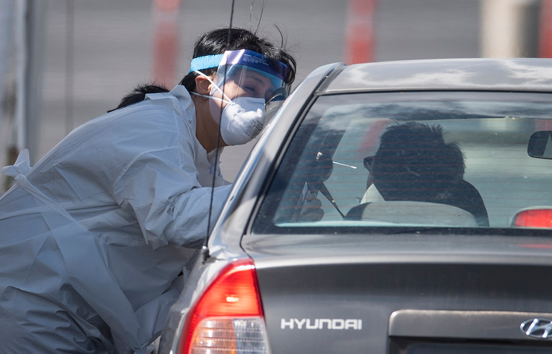 An employee from the Weld County Department of Public Health and Environment tests a man for the novel coronavirus at a drive-thru testing station for first responders at The Ranch events complex in Loveland, Colo. on Monday, March 30, 2020.