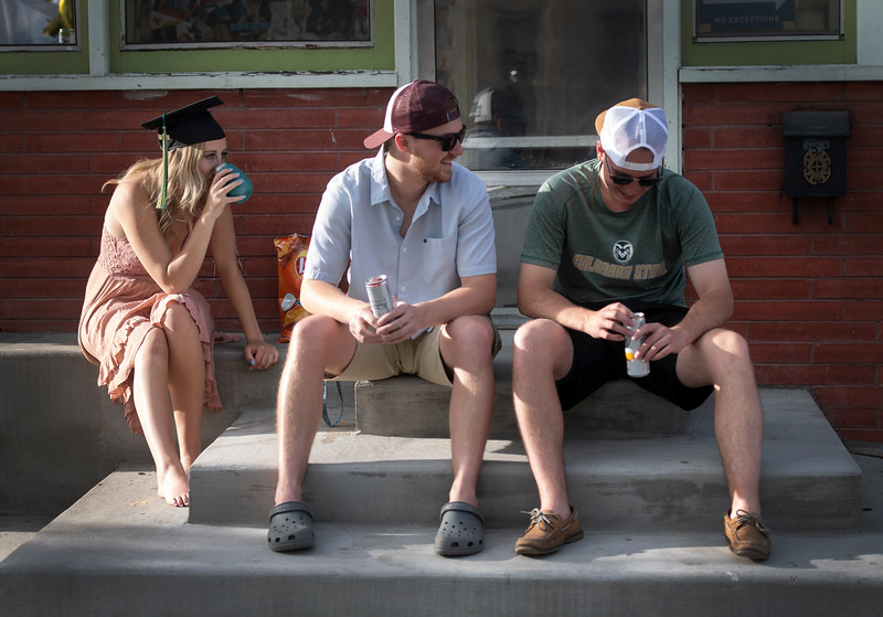 Three friends sit on their porch after a house party along South Howes Street during the Colorado State University graduation weekend in Fort Collins, Colo. on Saturday, May 16, 2020.