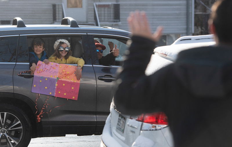 A car full of people wave and hold a sign for John Runkles, his wife Tasha Runkles, and their children during a homecoming parade to celebrate John's first day home after recovering from a severe stroke in Fort Collins, Colo. on Thursday, April 2, 2020. Due to the coronavirus pandemic, John could not receive more than one visitor in the hospital. Now that John is home, people must still maintain a social distance of at least six feet.