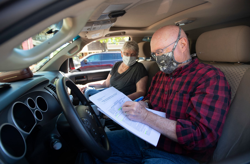 Ralph Smith signs paperwork to finish the sale of his home as his wife Janet Smith looks on in their truck in the parking lot outside an office for The Group in Fort Collins, Colo. on Friday, May 22, 2020.