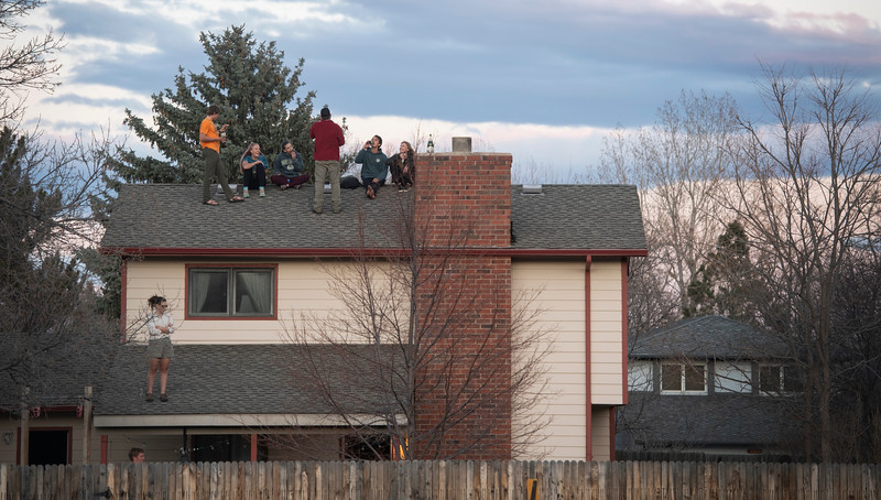 People gather on a rooftop to watch the sunset during the coronavirus pandemic in Fort Collins, Colo. on Tuesday, March 24, 2020.