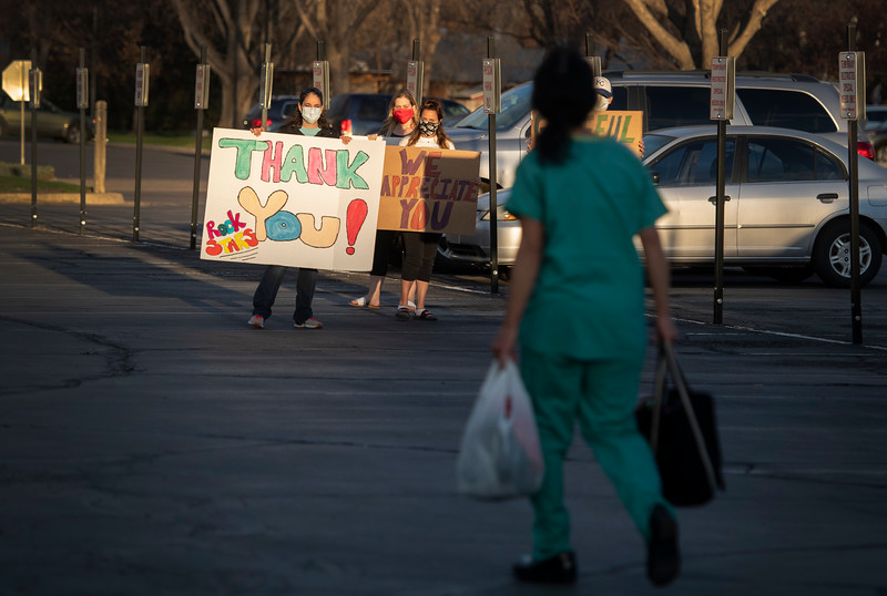 People hold signs thanking health care workers as a woman in scrubs walks through the parking lot outside UCHealth Poudre Valley Hospital during the coronavirus pandemic in Fort Collins, Colo. on Friday, March 10, 2020.