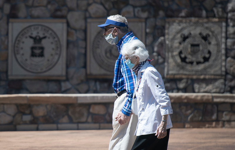 People wear masks as they walk through the Veterans Plaza of Northern Colorado over Memorial Day weekend in Fort Collins, Colo. on Monday, May 25, 2020.