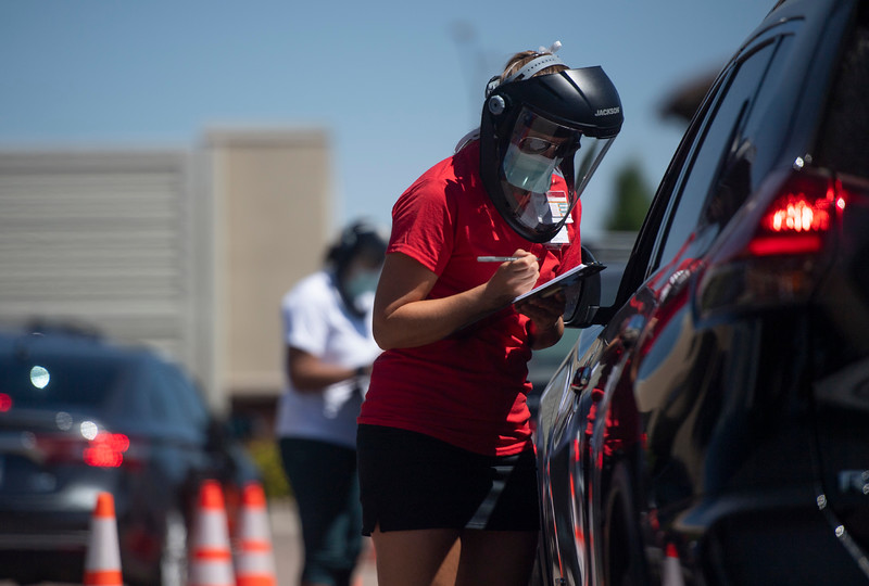 A staff member speaks with a motorist waiting in line at UCHealth's drive-through specimen collection center on the Harmony Campus in Fort Collins, Colo. on Wednesday, July 8, 2020.