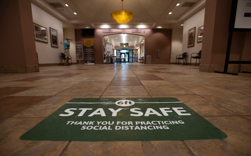 A sign on the floor encourages people to socially distance at the Larimer County Courthouse Offices Building in Fort Collins, Colo. on Wednesday, July 8, 2020.