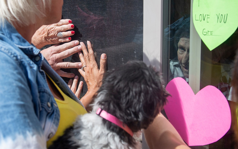 Evelyn Ford, 92, touches the glass as her family members do the same during their visit on Mother's Day at Lemay Avenue Health and Rehab Facility in Fort Collins, Colo. on Sunday, May 10, 2020.