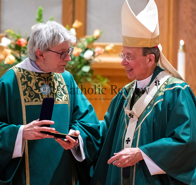 Archbishop William E. Lori, right, presents Deacon William R. Fleming III, director of Camp GLOW, the Culture of Life Medal of Honor during the Jan. 19 Life is Beautiful Mass at St. Joseph Church in Fullerton. (Kevin J. Parks/CR Staff)