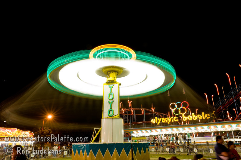 There are people hanging on swings under this spinning bright light<br /> Image taken at Tulare County Fair 9-17-2010