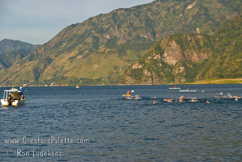 Guatemala Mission Trip - Day 3 -  Sunday, November 11, 2007<br /> Early Morning along shore of Lake Atitlan in Panajachel.   I heard American music on loud speakers and found this cold water distance swimming race.  As a former swimmer, I stayed to watch.  Swimmers were coated in grease or oil and then swam around 2 orange bouys set way out in the lake.  As unclean as we found the water, this did not seem like something I would want to do.