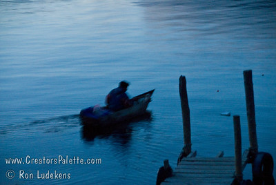 Guatemala Mission Trip - Day 7 - Thursday, November 15, 2007 Early morning on Lake Atitlan in Panajachel, Guatemala.  Local fisherman in his boat made of planks.  He did a lot of bailing water.
