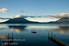Guatemala Mission Trip - Day 7 - Thursday, November 15, 2007<br /> Sunrise on Lake Atitlan in Panajachel, Guatemala.  Toliman Volcano with Atitlan Volcano behind it on left, San Pedro Volcano on right.  Local fisherman in his boat made of planks.  He did a lot of bailing water.