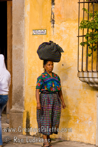 Guatemala Mission Trip - Day 8 - Friday, November 16, 2007<br /> Photo taken while walking down Calle del Arco towards Templo La Merced.  Guatemalan woman in traditional dress carrying a load on her head.  Antigua Guatemala.