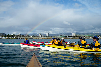 Paddling under the rainbow towards a pot of gold.