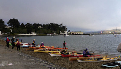 Kayakers gather on the beach.