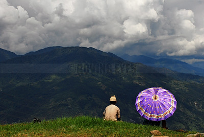 C19:The spectacle of clouds over the blue-green mountains hold the attention of locals,on a lazy afternoon in Pelling,West Sikkim