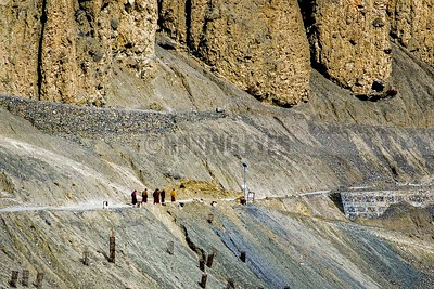 C28:Monks returning to their hostel from Dhankar Monastery in Spiti,Himachal Pradesh,dwarfed by the giant rocks overhanging the narrow path.