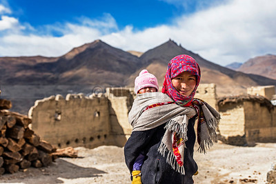 C30:A mother of Kibber village carries her child on her back on the way to her parents's place,in Spiti,Himachal Pradesh