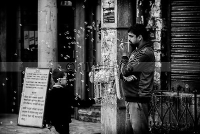 C21:A hawker blows soap bubbles as a schoolboy tries to touch the enticing beauties,in Darjeeling,West Bengal