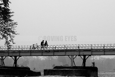 C4:Friends absorbed in chit-chat on the bridge across Murti river in Murti,West Bengal