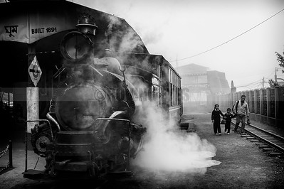 C14:The Toy Train emits steam waiting for passengers in the historic Ghum station(highest railway station in India at 2,258 metres)while a father brings his children back from school