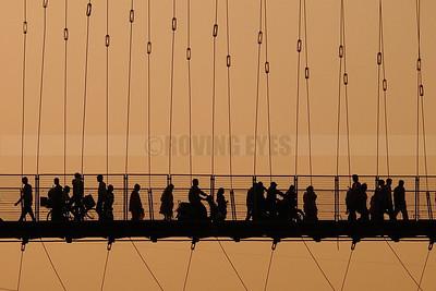 C5:People look like marionettes on strings crossing the Ramjhula bridge at dusk in Hrishikesh,Uttarakhand