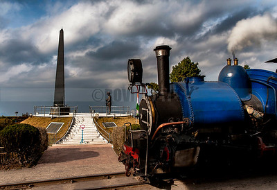 C15:Dramatic clouds gather in the sky as the Toy Train(Darjeeling Himalayan Railway) makes its customary stop at the Soldiers' Memorial at Batasia Loop in Ghum,Darjeeling,West Bengal.