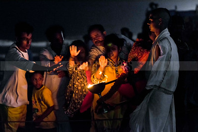 C24:People rush to take warmth from the holy fire after the evening 'arti' of the ocean on Puri beach,Odissa