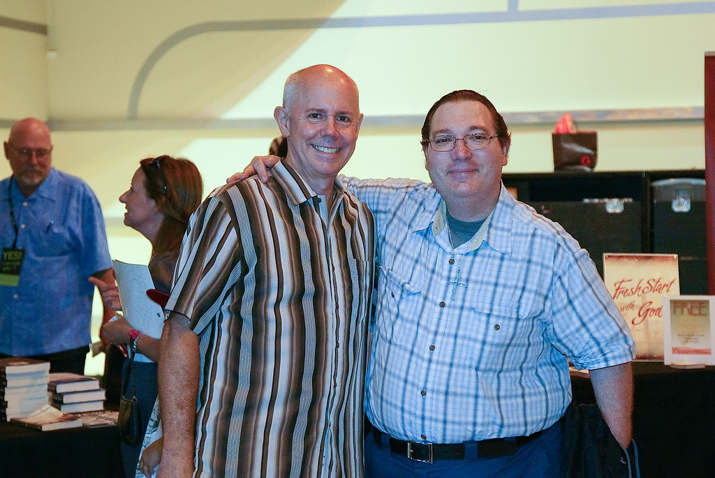 Pastor Tom Holladay posing with an individual at the Grove on Sunday July 8, 2012.