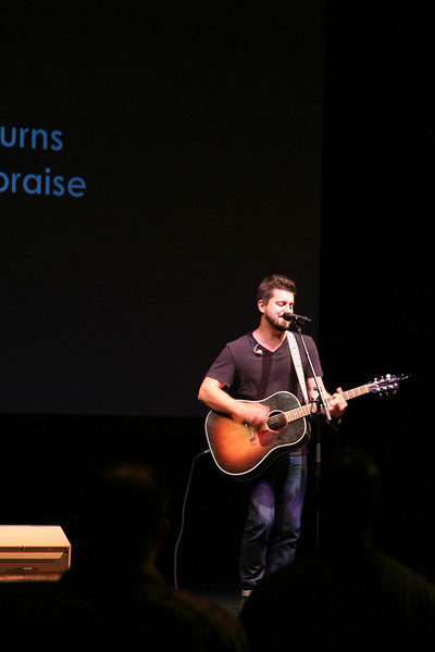 Travis Collins leading worship in song and playing his guitar.
