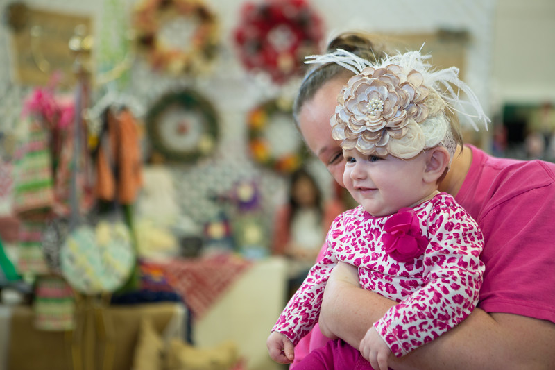 Hattye Claire Wright tries on a headband at the Razzberry Lane booth with her mother Hannah.