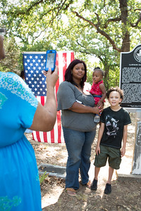 Danielle Holder of Peaster poses with Xia and Xavier near the historical marker. The children are among the seventh generation descendants of Lawson Gratz.