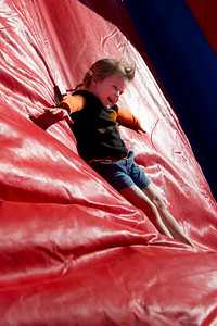 Kyla Ellis slides down the back of the inflatable climbing wall at First Baptist Willow Park during Park Fest.