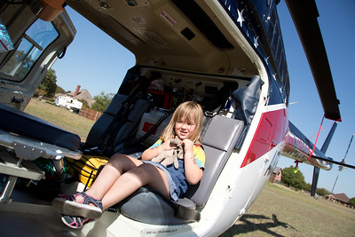 """Emma Patterson, 4, of Willow Park takes her elephant """"Nummy"""" aboard an air rescue helicopter on display at Willow Park Fest."""