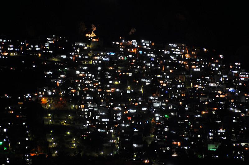 Nighttime over Damascus neighborhood built on steep mountain flank, Syria