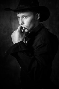 Portrait of handsome bearded cowboy wearing black hat and shirt, looking at camera, holding cigarette to lips.