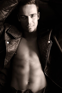 Semi naked handsome man sitting in leather armchair with open shirt revealing sixpack abs and open jeans