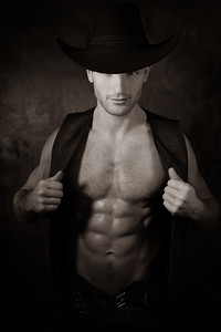 Handsome cowboy wearing hat with covered eye pulls open waistcoat to reveal defined pecs and muscular sixpack abs