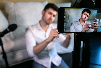 Young man recording video broadcast from home studio