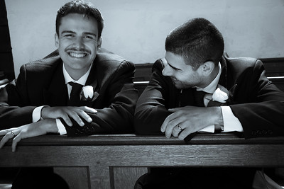 Gay male couple share a joke, laughing while waiting in church to be married.