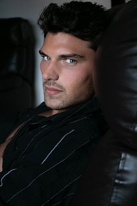 Portrait of attractive young man with blue eyes sitting in leather armchair looking at camera.