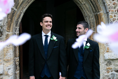 Smiling gay grooms leave church after getting married with confetti falling around them.