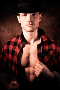 Portrait of handsome cowboy pulling chequered shirt open to reveal muscular pecs and defined sixpack abs