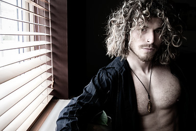Portrait of handsome man with beard and long hair standing next to window with sixpack abs, pecs
