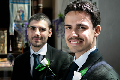 Smiling gay couple sitting and waiting in church to be married