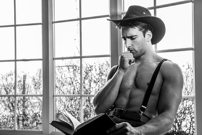 Portrait of handsome shirtless cowboy wearing hat sitting in window with book in lap, reading