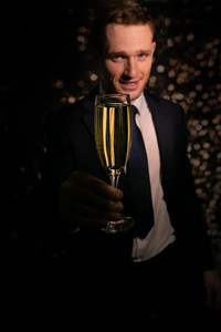 Good looking man in suit holding glass of sparkling wine in front of bokeh backdrop of lights