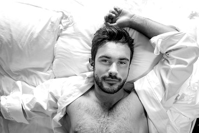 Portrait of handsome hairy muscular man with beard and open white shirt, looking up from bed at camera