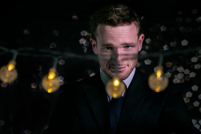 Good looking man in suit looking across string of lights with bokeh blurred lights in the background and room for copy