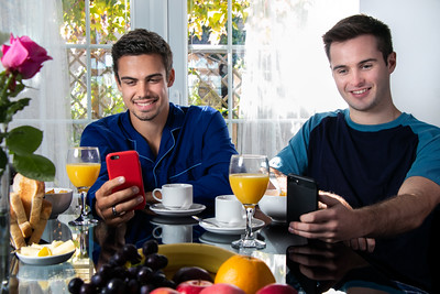 Friends or Gay couple sitting at breakfast table in front of patio doors looking at mobile devices and smiling