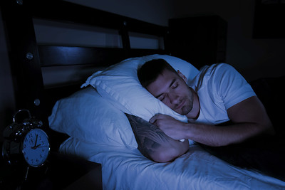 Handsome man looking at his mobile phone in bed at night with glow of phone lighting his face